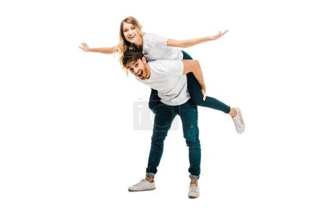 cheerful young couple piggybacking and smiling at camera isolated on white