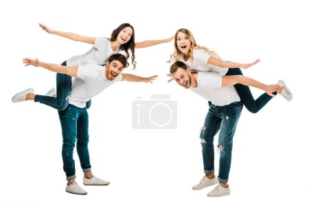 happy young couples piggybacking and smiling at camera isolated on white