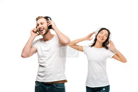 cheerful young couple in white t-shirts listening music in headphones isolated on white