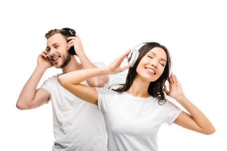 happy young couple in white t-shirts listening music in headphones isolated on white