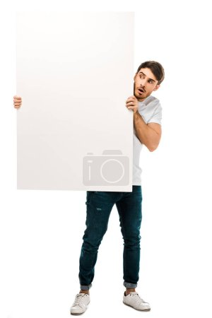 scared young man holding blank banner and looking at copy space isolated on white