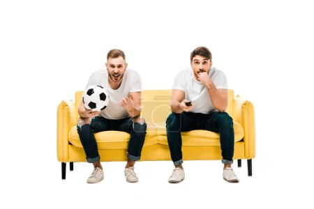 emotional young men with soccer ball sitting on couch and watching sports match isolated on white
