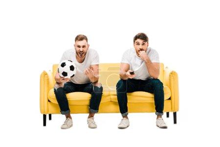 Foto de Emocionales jóvenes de fútbol pelota sentado en sofá y viendo deportes partido aislado en blanco - Imagen libre de derechos