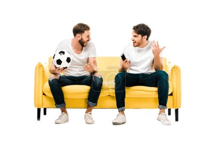 Photo for Happy young men with soccer ball and remote controller looking at each other isolated on white - Royalty Free Image