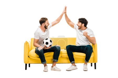 Photo for Happy young man sitting on couch with soccer ball and giving high five isolated on white - Royalty Free Image
