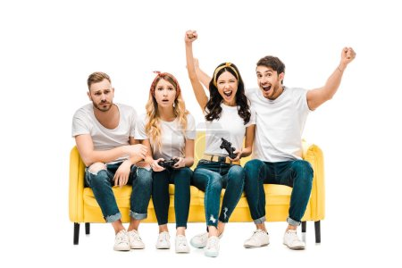 emotional young friends sitting on sofa and playing with joysticks isolated on white