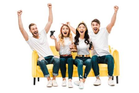 Foto de Excitada a joven amigos sentado en sofá y jugar con joysticks aislados en blanco - Imagen libre de derechos