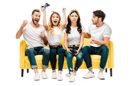emotional young friends sitting on couch and playing with joysticks isolated on white