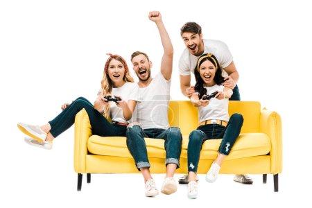 Foto de Excitada a joven amigos jugar con joysticks y sonriendo a cámara aislada en blanco - Imagen libre de derechos
