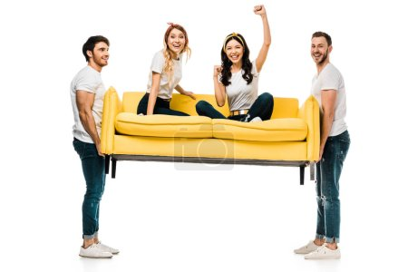 Photo for Cheerful young men carrying couch with beautiful girls sitting on it isolated on white - Royalty Free Image