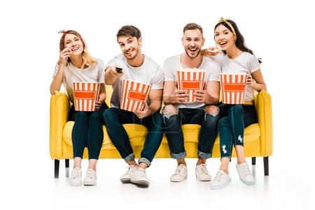 Photo for Happy young friends holding popcorn boxes and watching tv while sitting on yellow sofa isolated on white - Royalty Free Image
