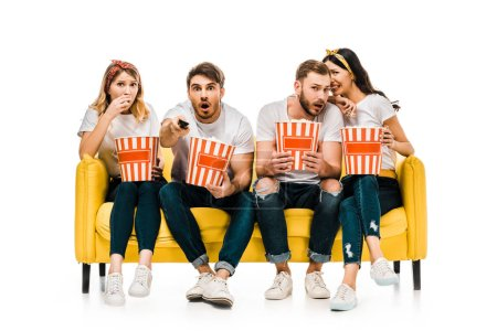 Photo for Shocked young friends eating popcorn from boxes and watching tv while sitting on yellow sofa isolated on white - Royalty Free Image