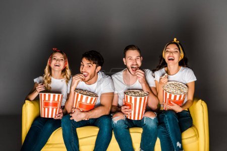 cheerful young friends sitting on yellow couch, watching movie and eating popcorn from boxes on grey