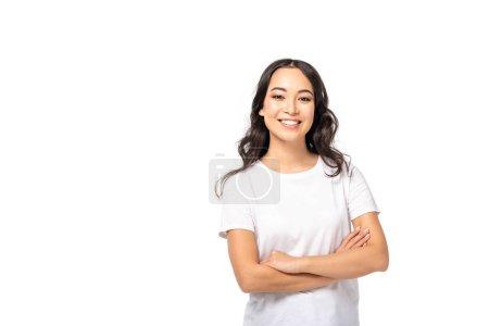 Sonriente asiática joven en camiseta blanca de pie con los brazos cruzados aislados en blanco