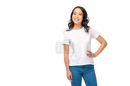 Photo pour Femme d'origine asiatique attrayante blanc t-shirt et jeans en tenant la main sur la hanche isolé sur blanc - image libre de droit