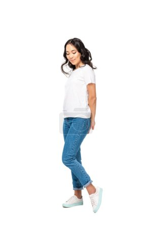 Confused asian woman in white t-shirt and blue jeans holding hands behind back isolated on white