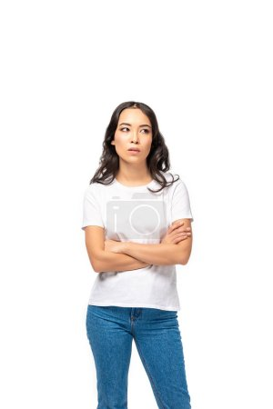 Thoughtful asian woman in white t-shirt and blue jeans standing with crossed arms isolated on white