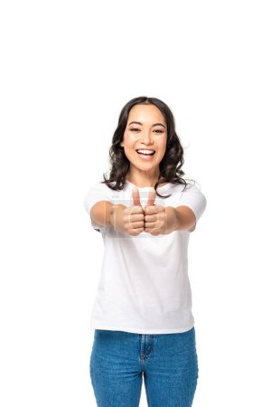 Photo for Smiling young asian woman holding hands together and showing thumbs up isolated on white - Royalty Free Image