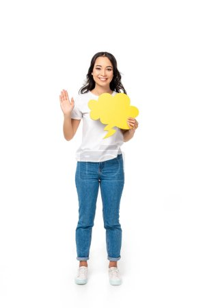 Photo for Smiling asian girl in white t-shirt and blue jeans holding empty thought bubble isolated on white - Royalty Free Image