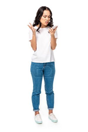 Photo for Angry asian girl in white t-shirt and blue jeans using smartphone isolated on white - Royalty Free Image