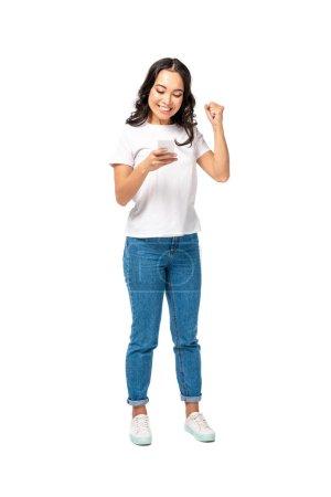 Foto de Sonriendo a feliz chica en camiseta blanca y jeans azules con smartphone y levantando el puño aislado en blanco - Imagen libre de derechos