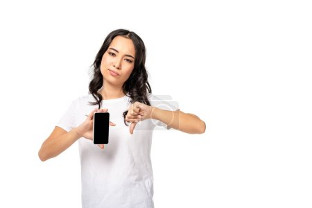 Photo for Unpleased asian woman holding smartphone with blank screen and showing thumb down isolated on white - Royalty Free Image