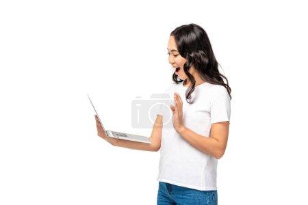 Photo pour Souriant jeune femme asiatique à l'aide d'un ordinateur portable et montrant geste bonjour isolé sur blanc - image libre de droit