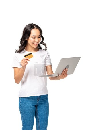 Photo for Smiling pretty asian woman in white t-shirt and blue jeans using laptop and holding credit card isolated on white - Royalty Free Image