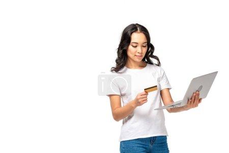 Photo pour Femme asiatique concentrée en t-shirt blanc et jeans bleus à l'aide d'un ordinateur portable et tenant la carte de crédit isolée sur blanc - image libre de droit