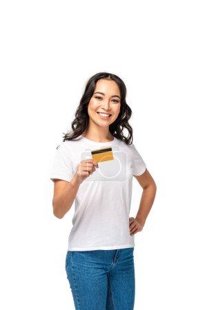 Photo pour Belle souriante asiatique femme montrant carte de crédit et tenant la main sur la hanche isolé sur blanc - image libre de droit