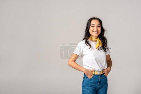 Photo pour Belles femmes asiatiques en t-shirt blanc et jean bleu avec les mains dans les poches isolées sur gris - image libre de droit