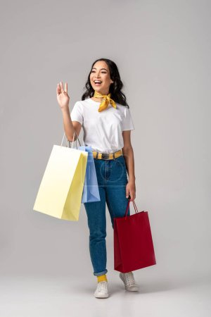 Photo for Trendy dressed young asian woman holding colorful shopping bags and waving by raised hand on grey - Royalty Free Image