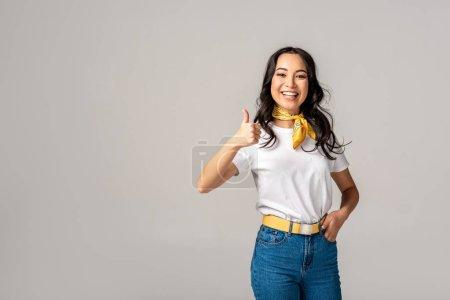 Photo pour Belle femme asiatique en vêtements colorés montrant le pouce vers le haut et regardant la caméra isolée sur fond gris - image libre de droit