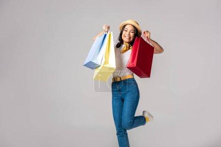 Photo pour Happy trendy habillé femme asiatique tenue colorés sacs à provisions sur mains surélevées isolés sur fond gris - image libre de droit