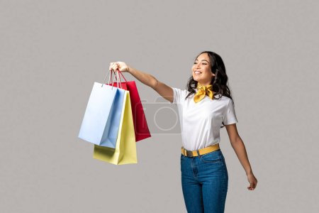Photo for Happy smiling asian girl holding colorful shopping bags in one stretched hand isolated on grey - Royalty Free Image