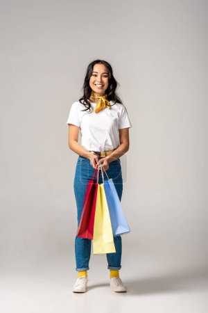 Photo for Attractive smiling asian woman holding colorful shopping bags on grey - Royalty Free Image