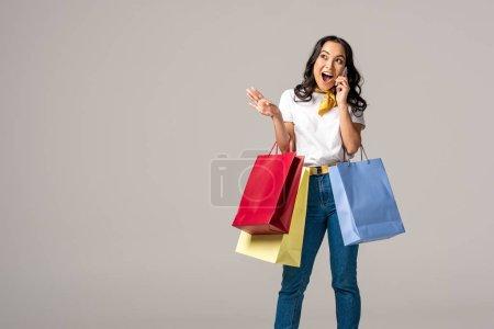Photo pour Jeune femme asiatique excitée maintenant colorés sacs à provisions et émotionnellement parlant sur smartphone isolé sur fond gris - image libre de droit