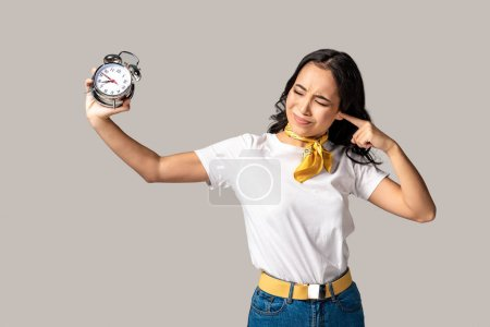Photo for Asian woman with closed eyes holding alarm clock in stretched hand and closing ear with forefinger isolated on grey - Royalty Free Image
