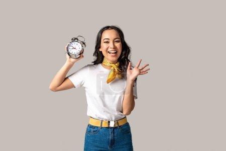 Foto de Feliz mujer asiática en camiseta blanca y pantalones vaqueros azul sosteniendo despertador y agitando la mano aislado en gris - Imagen libre de derechos