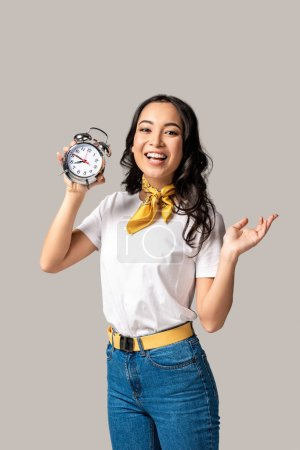smiling young asian woman in white t-shirt and blue jeans holding alarm clock isolated on grey