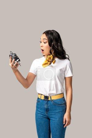 Photo pour Surpris de jeune femme asiatique en blanc t-shirt et jeans en tenant le réveil isolé en gris - image libre de droit