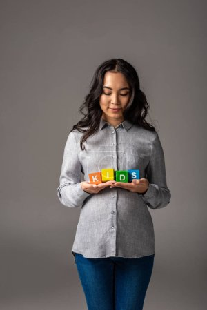 Photo for Smiling pregnant young asian woman holding alphabet cubes with word kids isolated on grey - Royalty Free Image