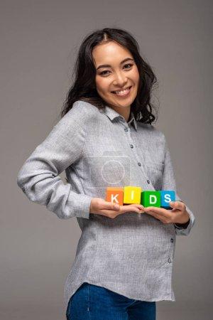 Photo pour Enceinte jeune asiatique femme tenant alphabet cubes avec mot enfants isolé sur gris - image libre de droit