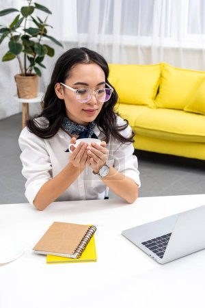 Photo for Smiling asian freelancer sitting at work desk and holding cup of coffee - Royalty Free Image