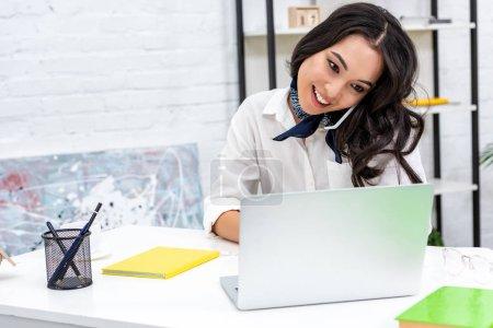 Photo pour Belle pigiste asiatique souriante à l'aide d'ordinateur portable et de parler au smartphone tout en étant assis au bureau à la maison - image libre de droit