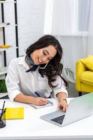 Foto de Wrtiting freelance bastante asiática en el cuaderno usando laptop y hablando por teléfono inteligente - Imagen libre de derechos
