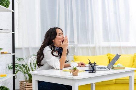 Photo pour Somnolent asiatique freelance assis à l 'bureau et bâiller avec couvrant bouche avec main - image libre de droit