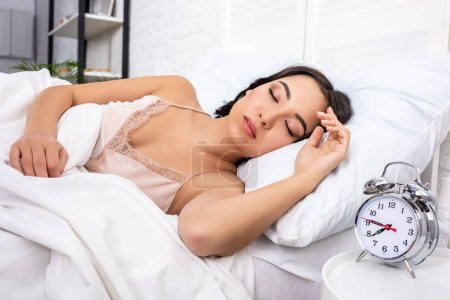 Photo for Beautiful young woman in elegant nightie sleeping on white bedding while alarm clock showing quarter to eight in morning - Royalty Free Image