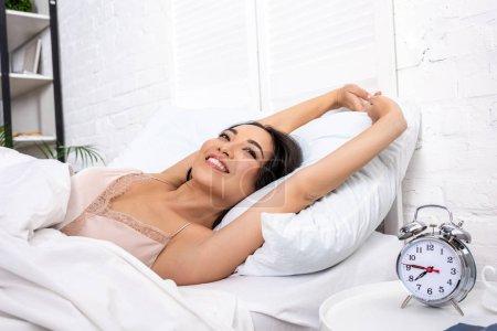 Photo pour Femme souriante éveillée en nuisette élégante se trouvant sur la literie blanche et d'étirements - image libre de droit
