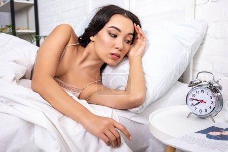Photo pour Belle jeune femme portant sur une literie blanche matin, regardant réveil montrant trimestre à huit - image libre de droit